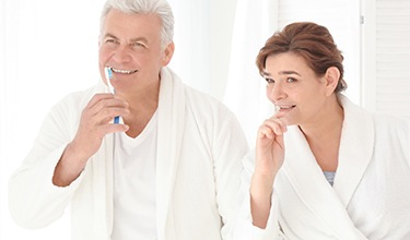 Older couple brushing teeth together