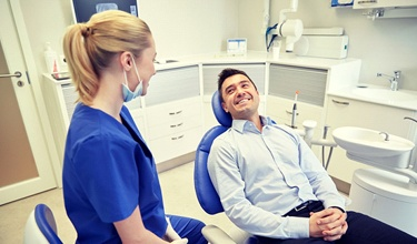 man smiling with dental hygienist