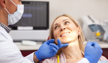 woman is chair smiling during dental appointment
